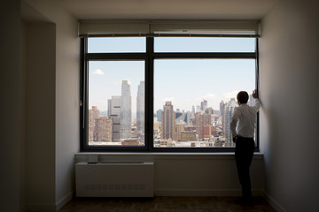 Rear view of man looking through window while standing in office corridor