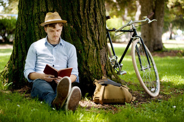 Young man reading book under tree