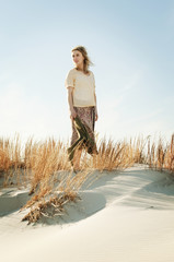 Young woman standing on dunes on beach