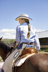 Cowgirl on her horse wearing chaps and cowboy hat