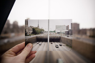 Hand holding picture of highway in front of highway