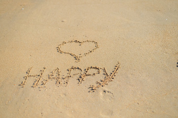 Love heart and happy word, honeymoon or valentine's day greetings on the sand