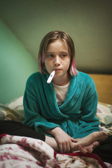 Girl (10-11) with thermometer in bed
