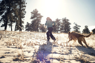 Low angle view woman with dog running on snow covered field