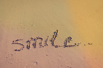 Abstract sign of word smile written, sand beach background
