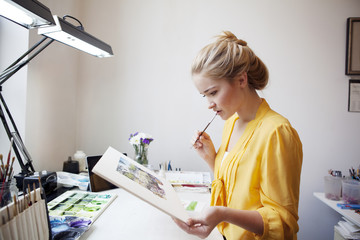 Young woman working in painting studio