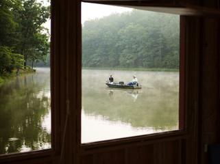 Two men fishing on lake