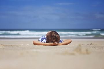 Boy (2-3) lying on sandy beach