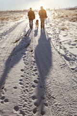 Two hunters walking down snowy trail with dog