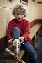 Boy (6-7) putting on ice skate in locker room