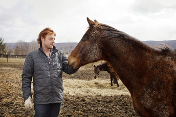Man petting a horse in a field