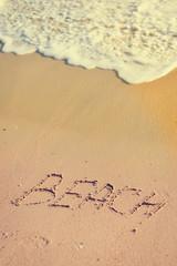 Beach sign on sandy ocean foam wave coastline