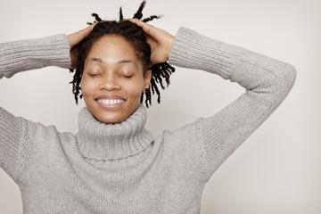 Portrait of woman pushing hair back
