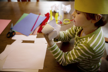 High angle view of boy making origami fortune teller at table