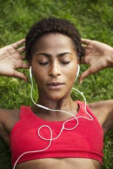 High angle view of woman listening music while exercising on field