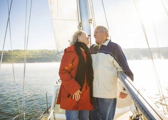 Happy senior couple standing in yacht on sea during summer