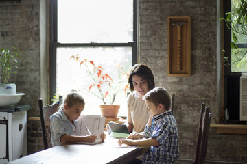 Mother assisting children in doing homework while sitting at table