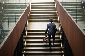 Rear view of businessman walking up on stairs