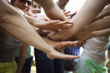 Close up of people stacking hands together