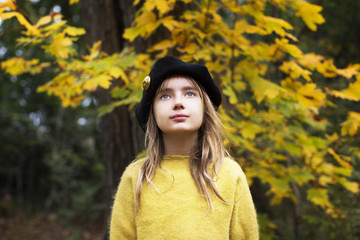 Thoughtful girl looking away while standing in park during autumn