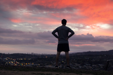 Rear view of silhouette athlete standing on mountain during sunset