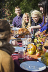 Woman serving roasted chicken to friends at outdoor table during garden party