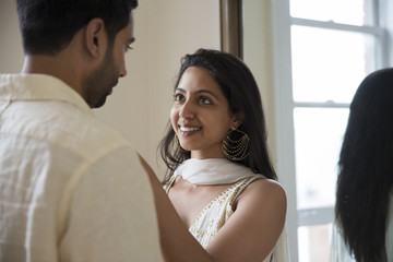 Couple looking at each other while standing against mirror