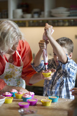 Boy with grandmother filling cupcake holders in kitchen