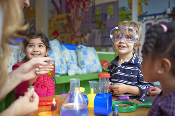 Happy children doing science experiment at table in preschool
