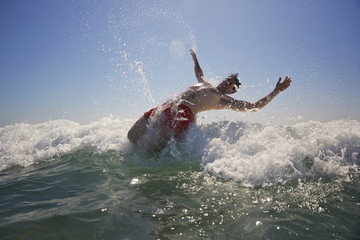 Man falling in sea against clear sky