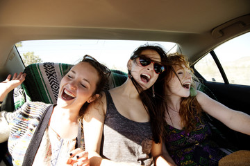 Cheerful female friends traveling in car