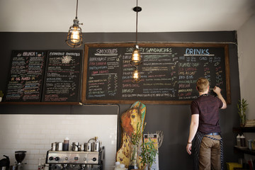 Rear view of man writing on blackboard at cafeteria