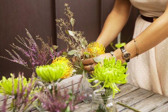 Woman arranging flowers in jars on a wooden table
