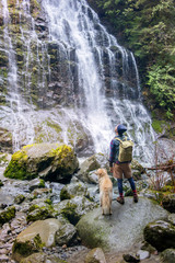 Man standing with dog against waterfall