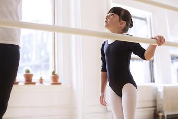 Cute ballerina looking at male teacher in studio