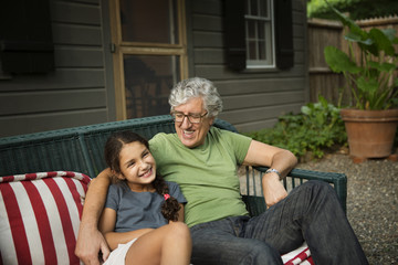 Happy grandfather and granddaughter sitting on wicker sofa at yard