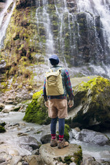 Rear view of hiker with backpack standing against waterfall