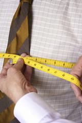 Cropped image of man examining tape measure