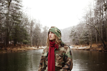 Man looking away while standing against lake during winter