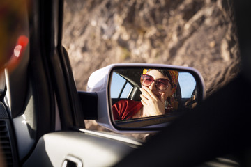 Woman smiling seen through side-view mirror of car