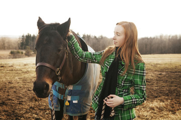 Teenage girl stroking horse while standing on field against clear sky