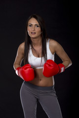 Long dark hair beautiful girl with red boxing gloves on her hands and fitness dress ready for exercise