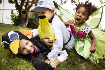 Happy children in Halloween costumes playing on grass