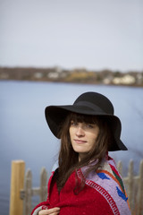 Portrait of smiling woman wearing hat wrapped in blanket standing by lake