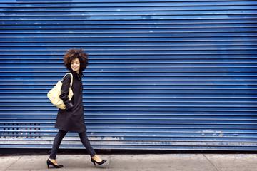 Full length of smiling woman walking on sidewalk by blue shutter