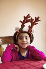 Portrait of happy girl wearing reindeer headband while sitting at table