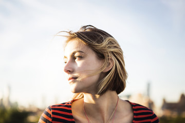 Close-up of thoughtful woman against clear sky on sunny day