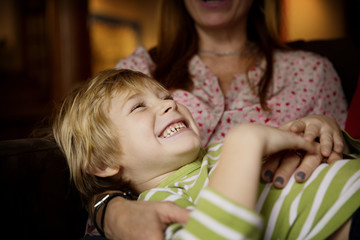 Cheerful boy with mother at home
