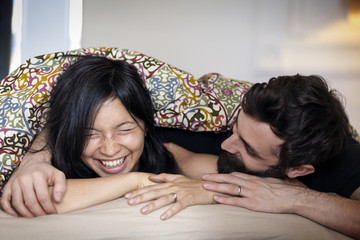 Happy couple talking while lying on bed at home