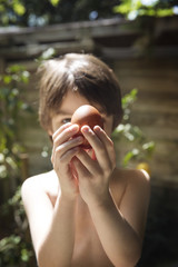 Shirtless boy holding egg while standing in backyard